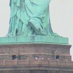 Woman Climbs up Statue of Liberty Base